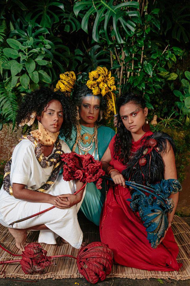 Trio musical Clarianas: Naruna Costa com as parceiras Martinha Soares e Naloana Lima - todas mulheres negras, vestindo roupas coloridas