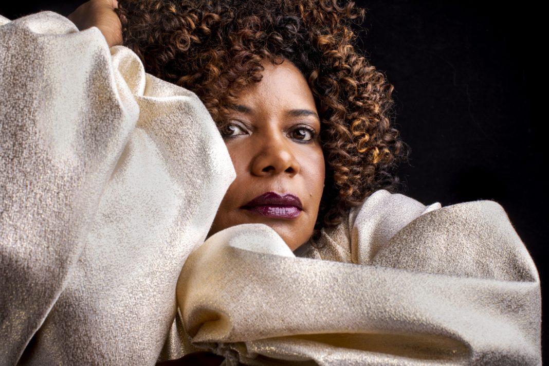 Margareth Menezes - mulher negra de cabelo cacheado, usando roupa beje- sentada com a mão esquerda apoiando o rosto