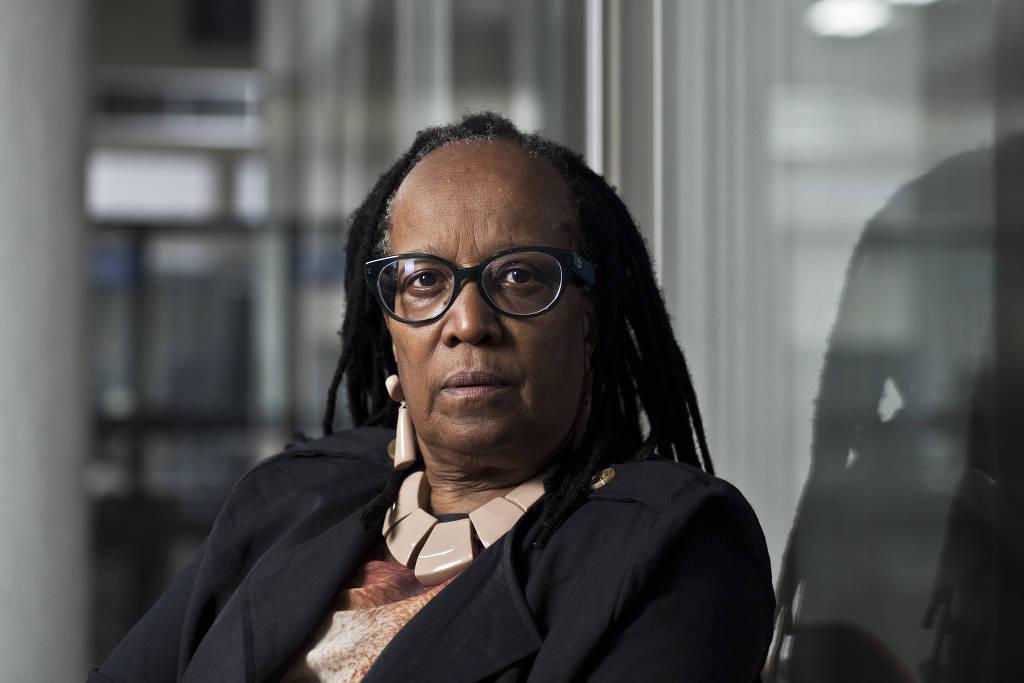 Sueli Carneiro - mulher negra, usando óculo de grau - sentada olhando para frente