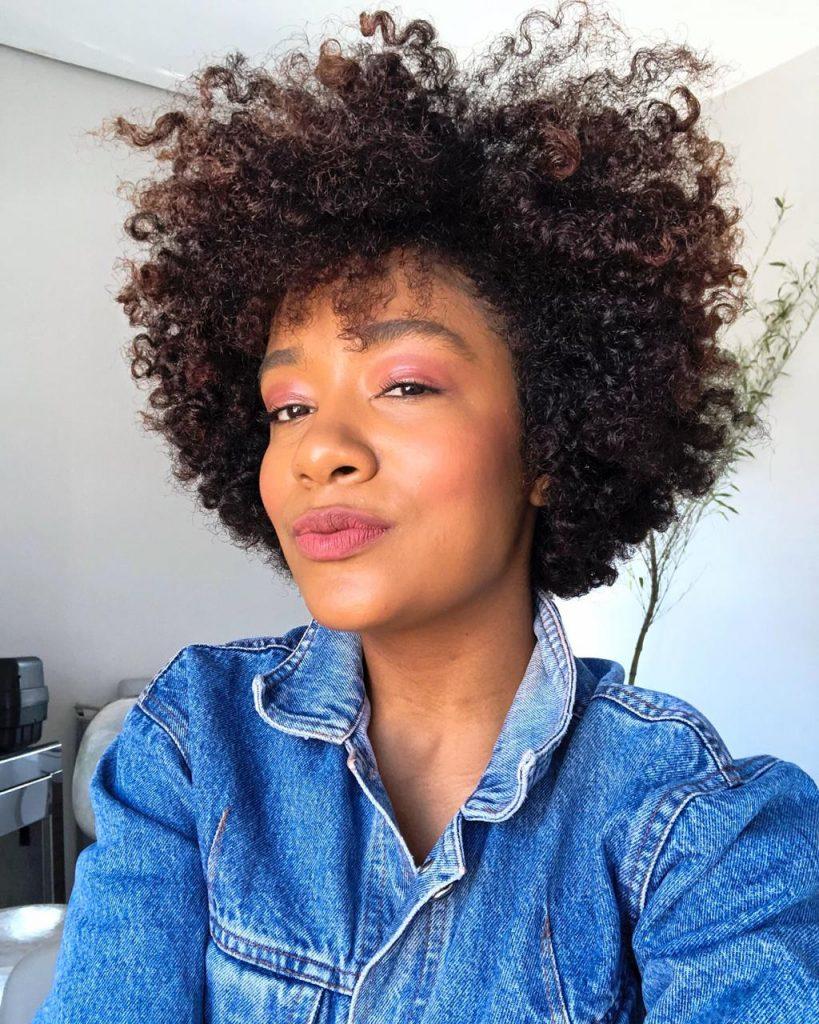 Selfie de Sah Oliveira- mulher negra, de cabelo crespo, usando camiseta jeans.