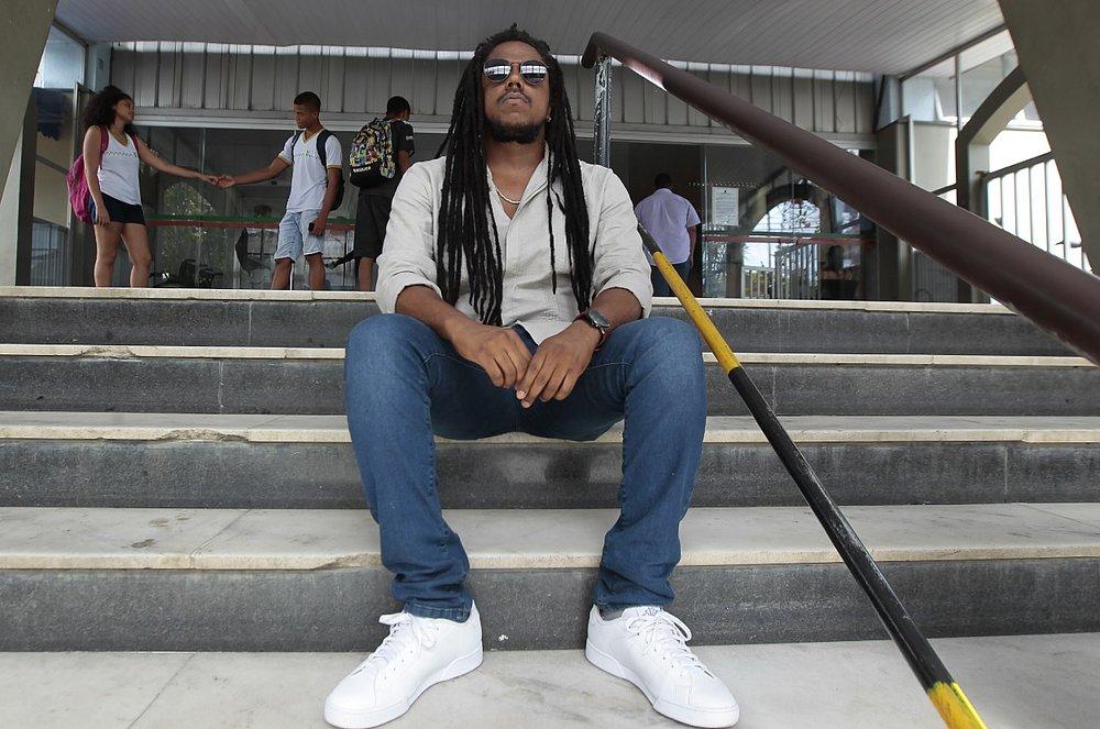 Miguel - homem negro de dreads, usando camiseta e calça jeans - sentado em uma escada