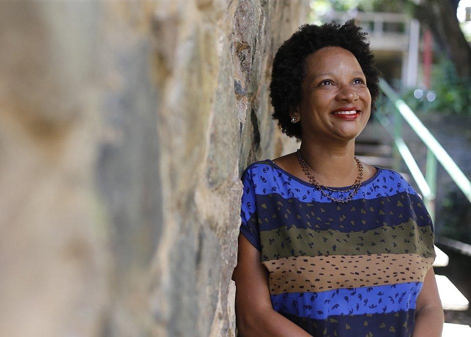 Cássia Maciel - mulher negra de cabelo curto e crespo, usando camiseta colorida- em pé olhando para cima e sorrindo
