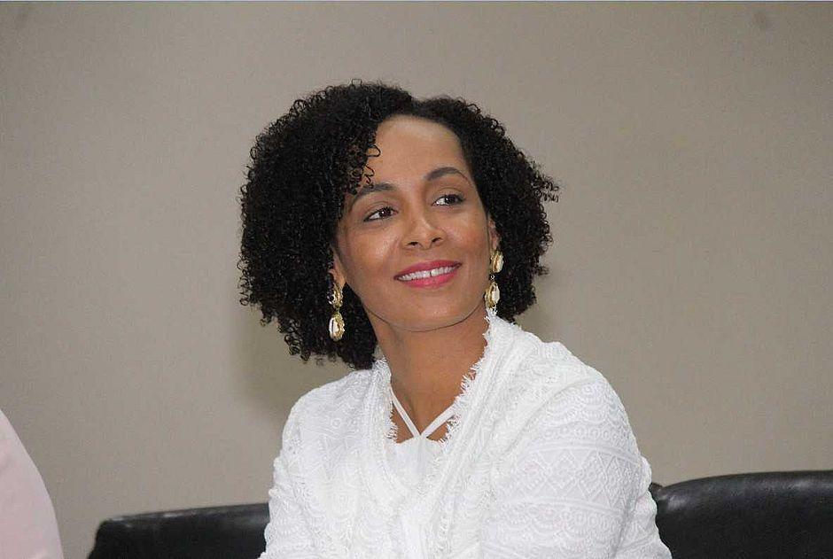 Lívia Vaz - mulher negra de cabelo cacheado, usando camisa branca e batom rosa- sentada sorrindo