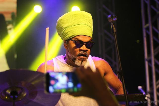 Carlinhos Brown - homem negro de barba grisalha, usando camiseta branca e turbante verde- tocando durante um show