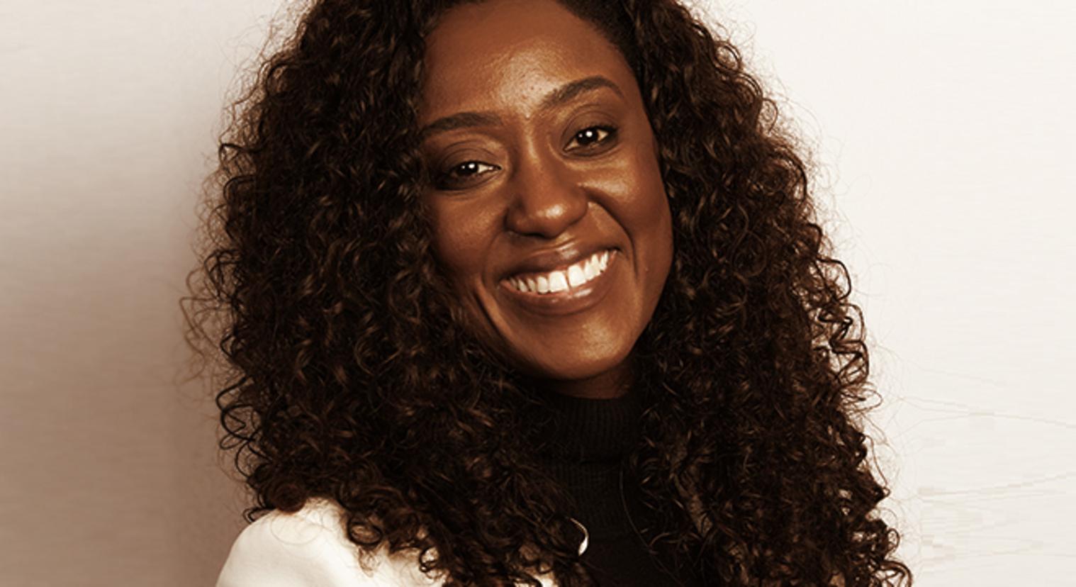 Fernanda Leôncio - mulher negra, de cabelo cacheado - sorrindo
