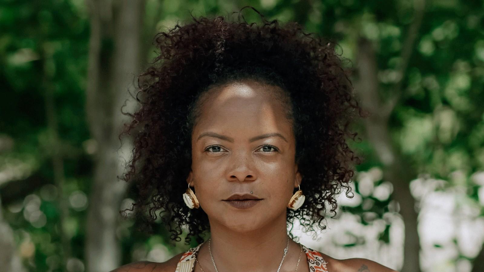 Lívia Natáli - mulher negra de cabelo cacheado, usando camiseta colorida e batom marrom - em pé olhando para frente