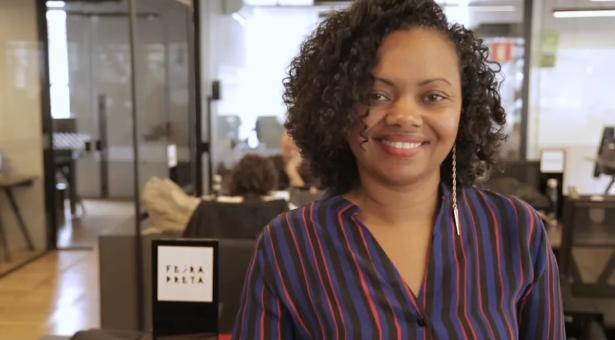 Adriana Barbosa - mulher negra, usando camiseta listrada roxa- em pé sorrindo