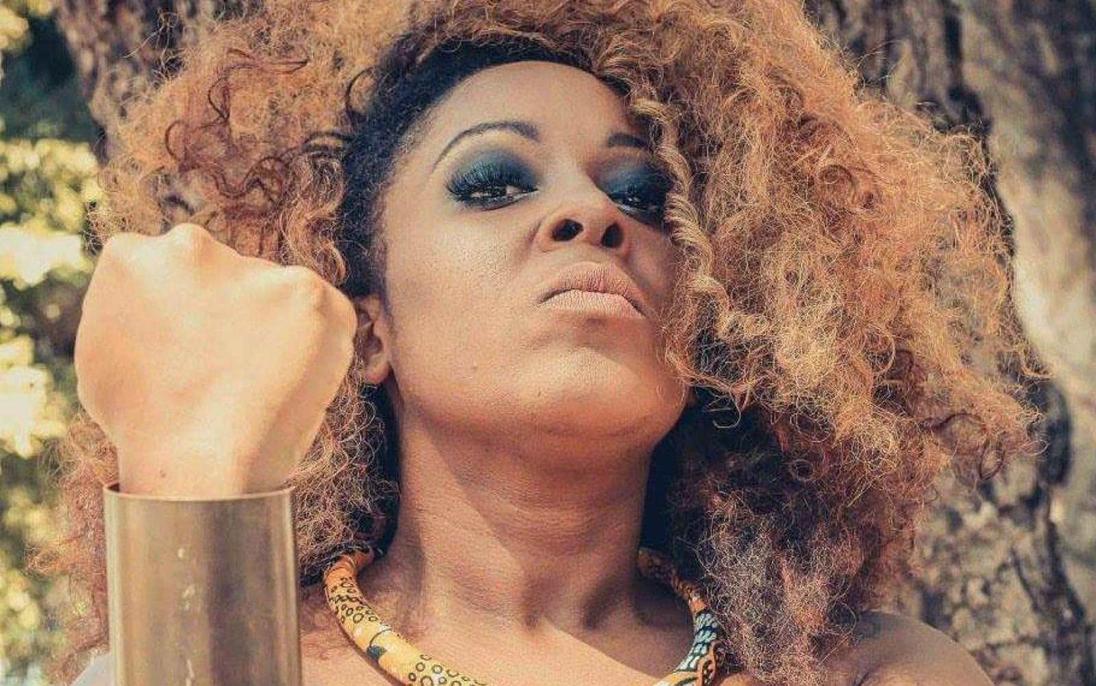 Maíra Azevedo - mulher negra de cabelo cacheado- em pé olhando para baixo