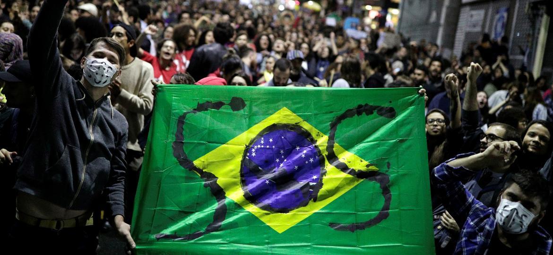 Manifestantes fazem protesto escrevendo S.O.S na bandeira do Brasil em São Paulo Imagem: Nacho Doce/Reuters