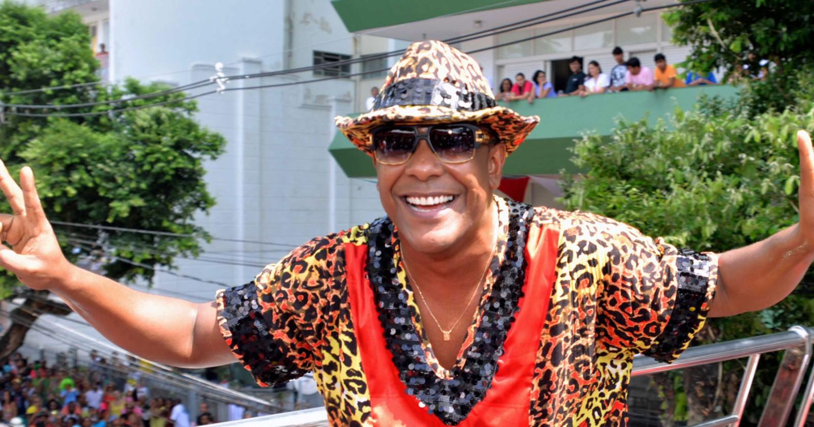 Márcio Victor - homem negro usando, óculos de sol, camiseta e chapéu colorido- em pé sorrindo