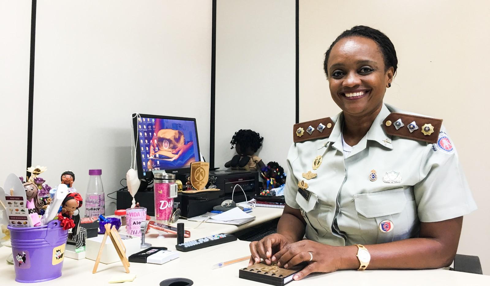 Major Denice Santiago - mulher negra de cabelo, preso, usando uniforme de major- sentada diante de uma mesa de escritório