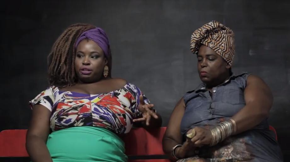 Duas mulheres negras sentadas e um sofá vermelho