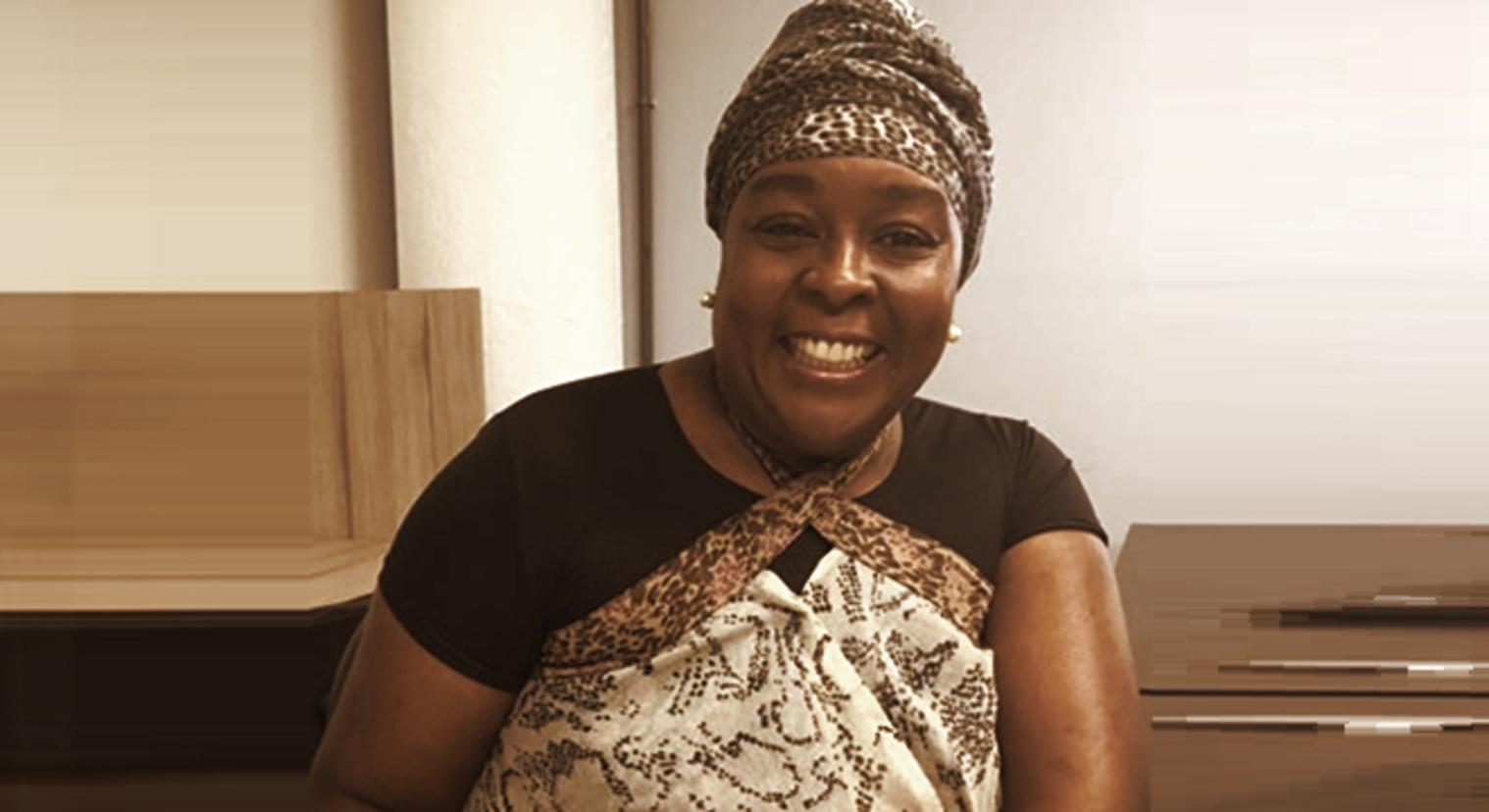 Regina Celia - mulher negra, usando turbante e blusa marrom - sentada sorrindo
