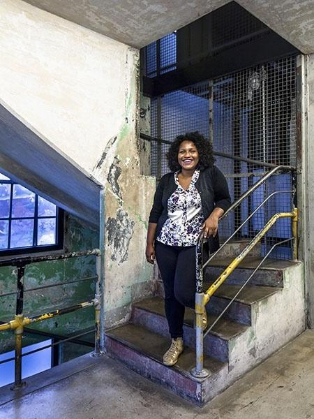 Silvana Bahia- mulher negra, de cabelo cacheado- em pé em uma escada