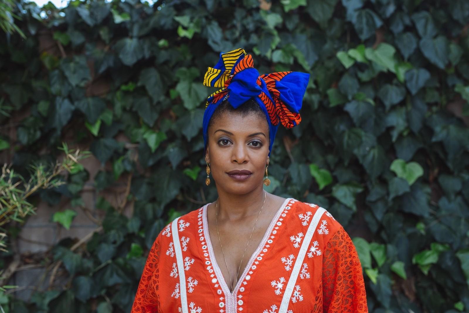 Thalma de Freitas - mulher negra, usando turbante azul marinho e camiseta laranja- em pé olhando para frente