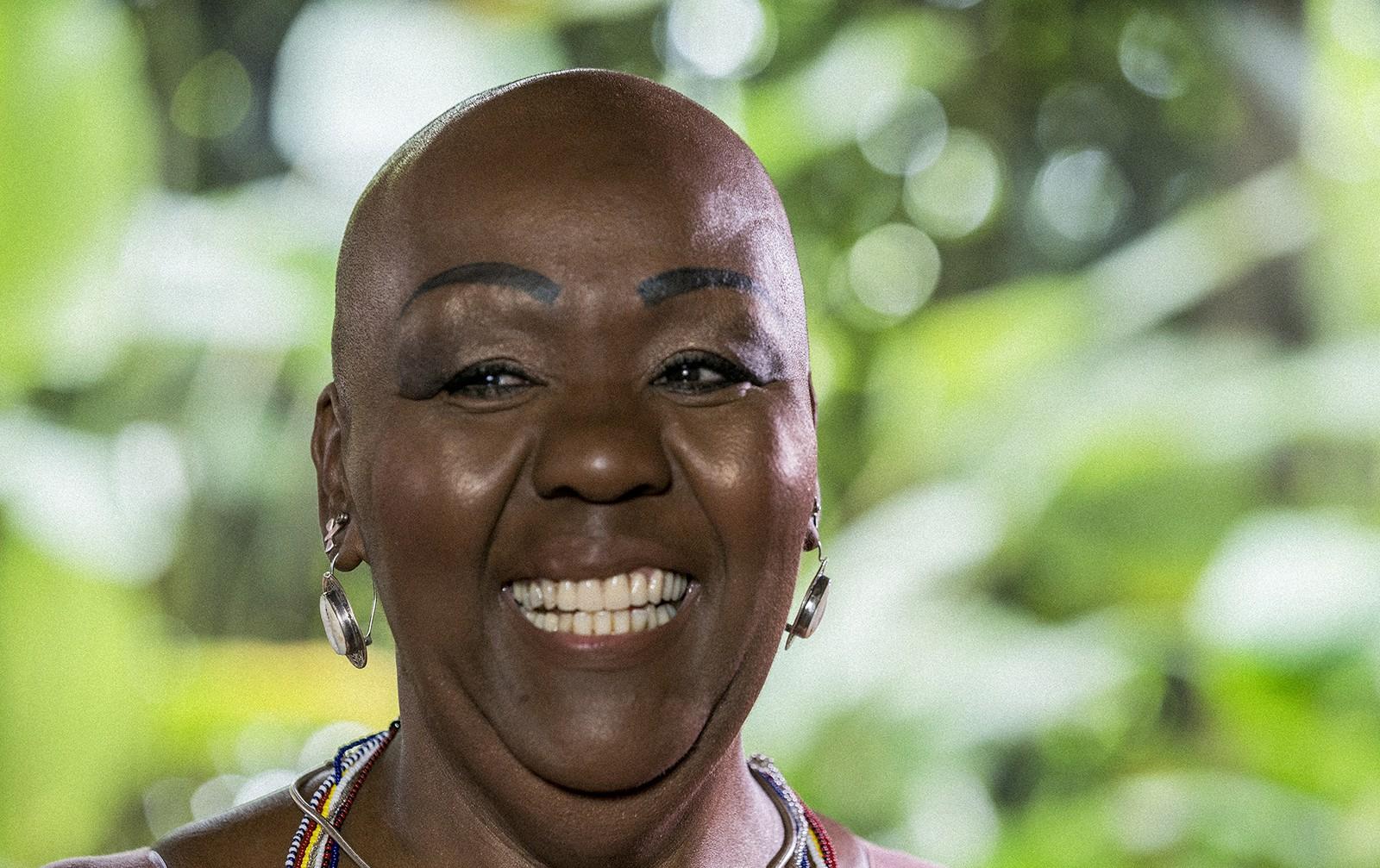 Virgínia Rodrigues - mulher negra, careca- em pé sorrindo