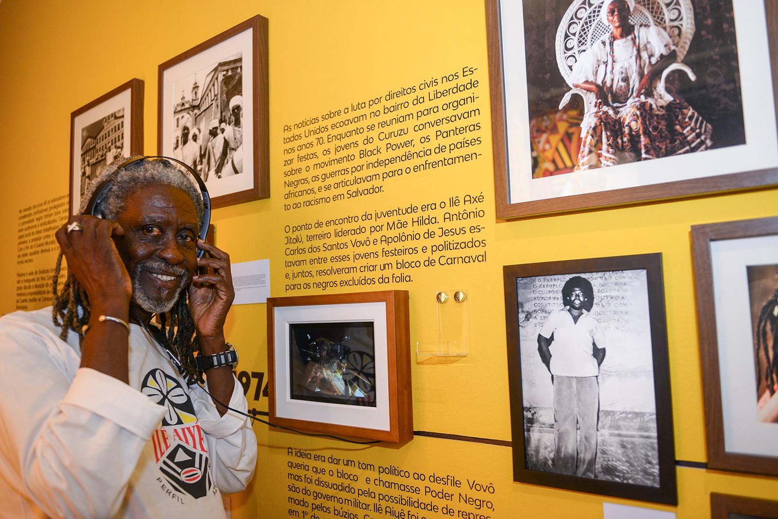 Vovô do Ilê- homem idoso negro, de dreads grisalho, usando fone de ouvido- em pé sorrindo