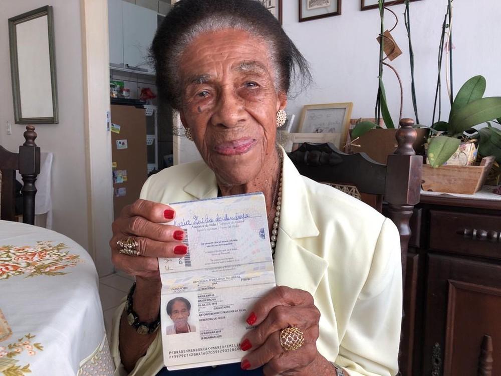 Maria Emília - mulher negra idosa, de cabelo grisalho, usando terninho branco- sentada segurando seu passaporte de 102 anos