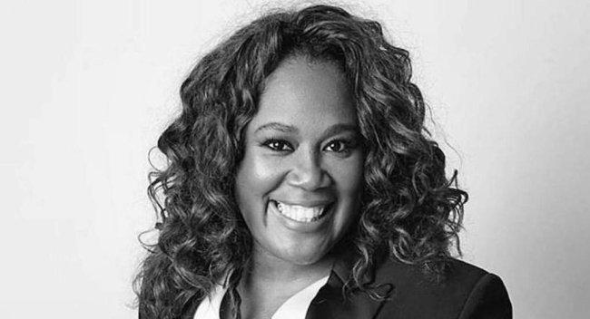 Foto em preto e branco de Katleen Conceição - mulher negra de cabelo cacheado, usando terno- em pé sorrindo