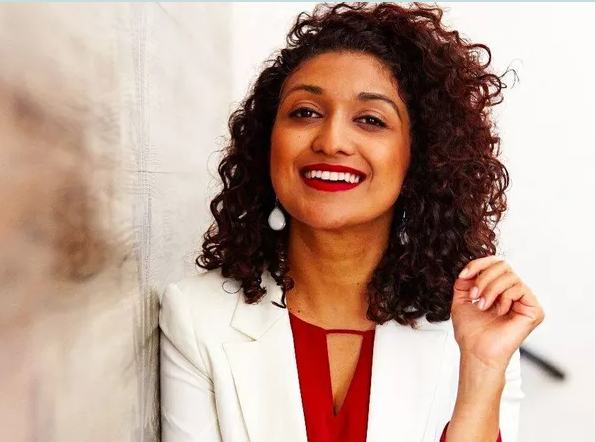 Viviane Duarte - mulher negra de cabelo cacheado, vestindo terninho branco e camiseta vermelha- em pé sorrindo