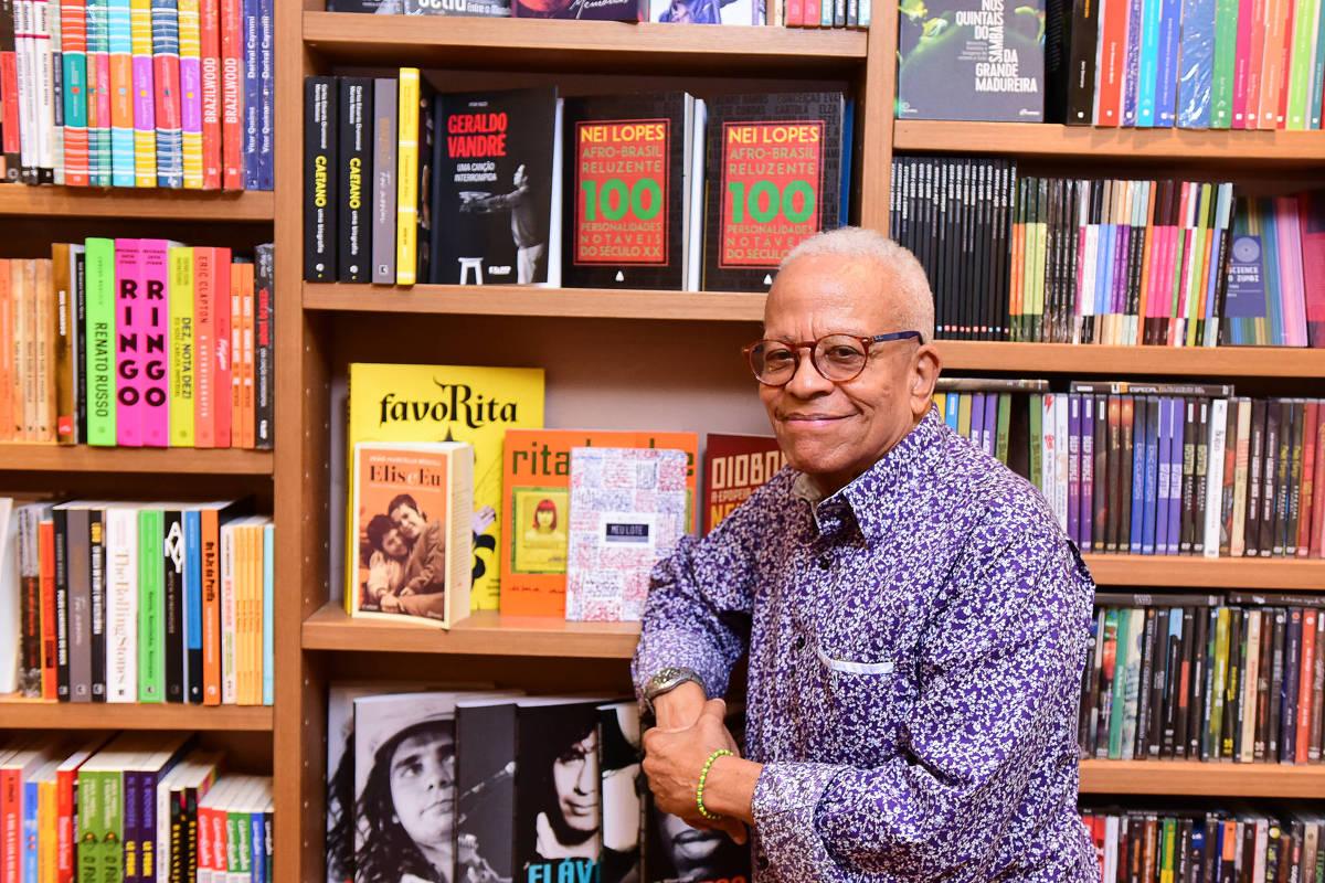 Nei Lopes ao lado de uma estante cheia de livros
