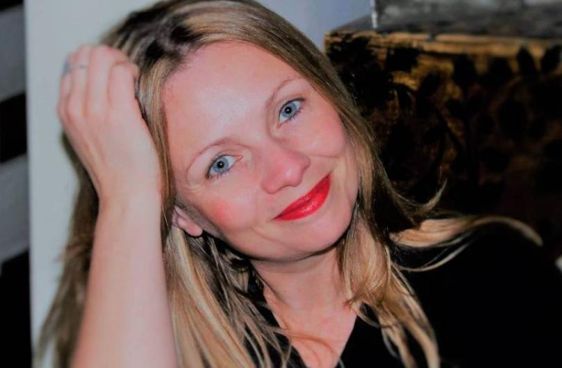 Nara Vidal - mulher branca, de cabelo longo e loiro e cor dos olhos azul, usando camiseta preta e batom vermelho- sentada apoiando a mão diteira na cabeça