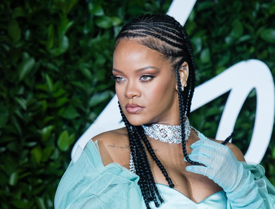 Rihanna- mulher negra de tranças, usando vestido e luvas cor verde água- olhando para frente