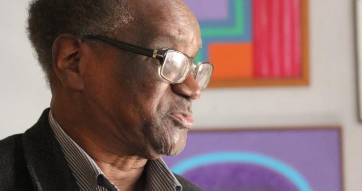 Oswaldo de Camargo - homem idoso negro de pouco cabelo, usando óculos de grau e roupa social.