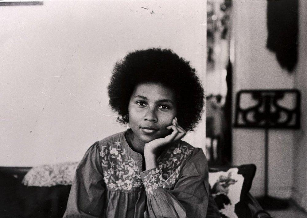 Foto em preto e branco de belll hooks quando jovem,- mulher negra de cabelo black, vestindo camiseta larga- sentada com a mão esquerda apoiando o rosto