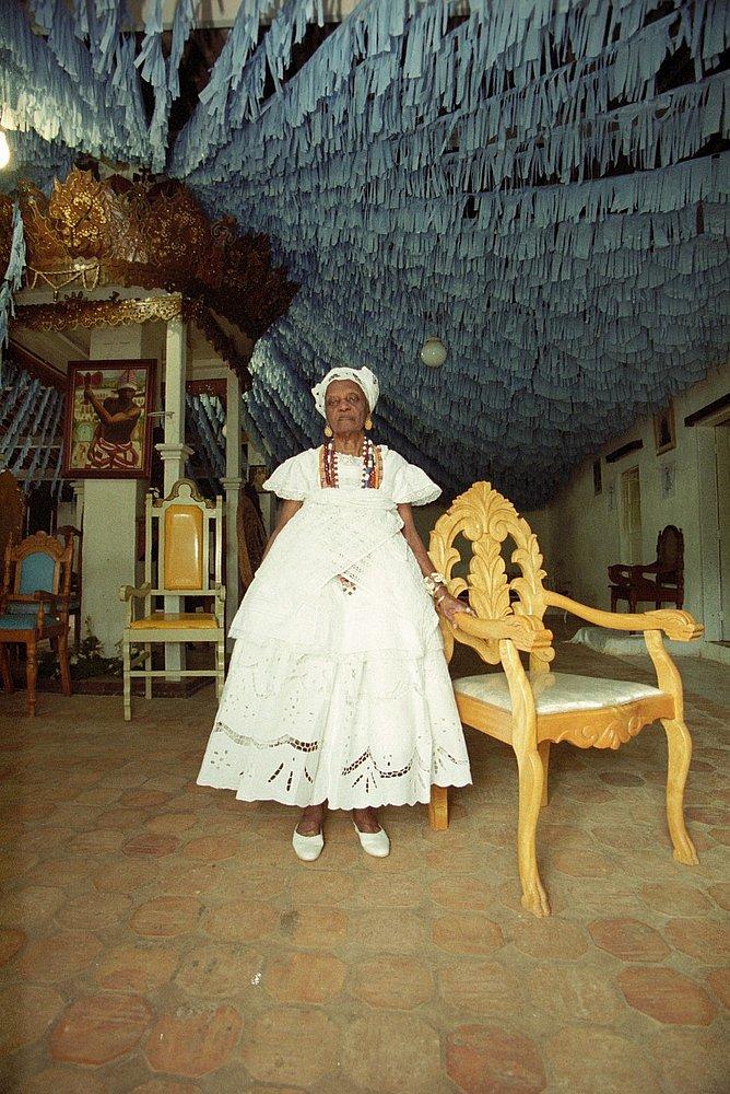 Mãe Tatá de Oxum- mulher negra idosa, vestino vestimentas brancas- em pé ao lado de uma cadeira