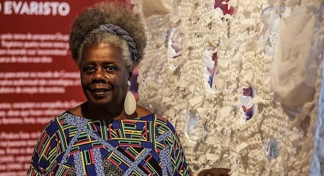 Conceição Evaristo- mulher idosa nera, de cabelo grisalho crespo, usando camiseta colorida e brincos grandes - em pé sorrindo