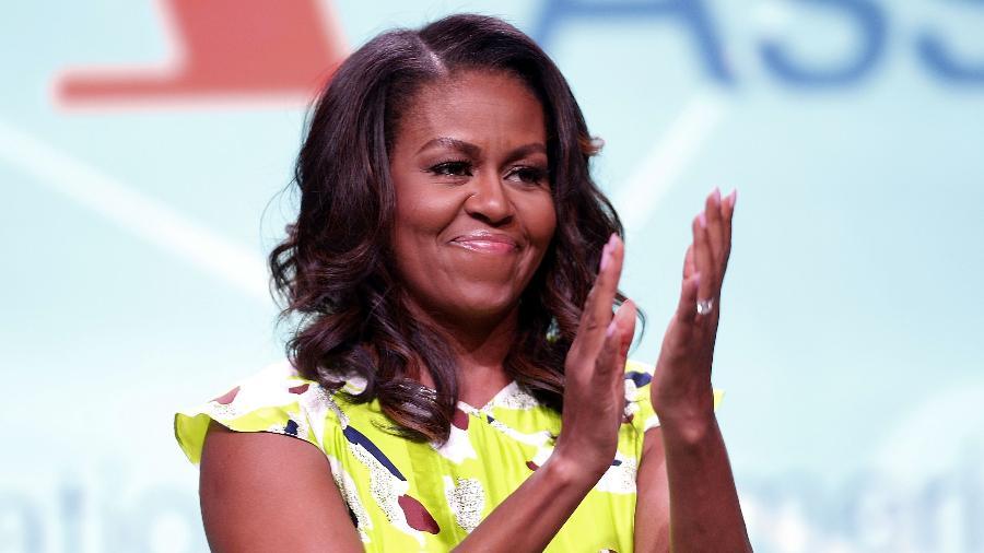 Michelle Obama- mulher negra, de cabelo liso, usando camiseta amarela com estampas coloridas- aplaudindo