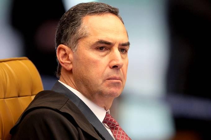 Luís Roberto Barroso- homem branco de cabelo grisalho, vestindo terno e gravata- sentado