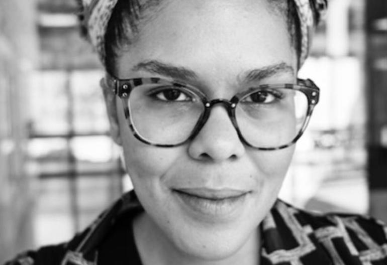 Foto em preto e branco de Djamilia Pereira de Almeida- mulher, usando óculos de grau e dando em leve sorriso de canto de boca.