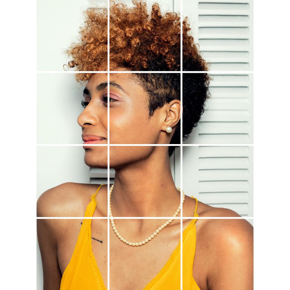 Stephanie Ribeiro- mulher negra de cabelo curto, vestimco regata amarela- em pé olhando para o lado