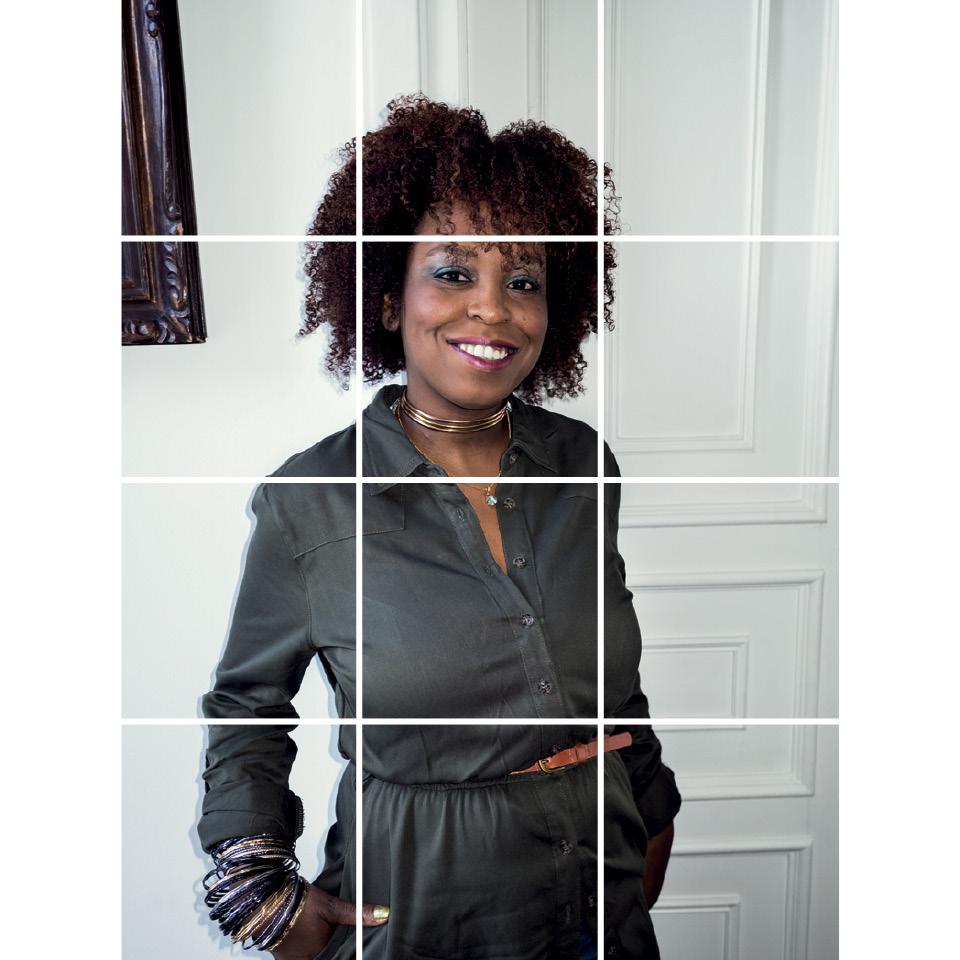 Joice Berth-- mulher negra, de cabelo crepo, vestindo macação cinza- em pé sorrindo