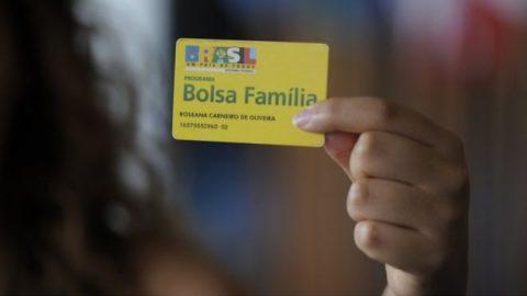 Uma mão segurando o cartão do Bolsa Família
