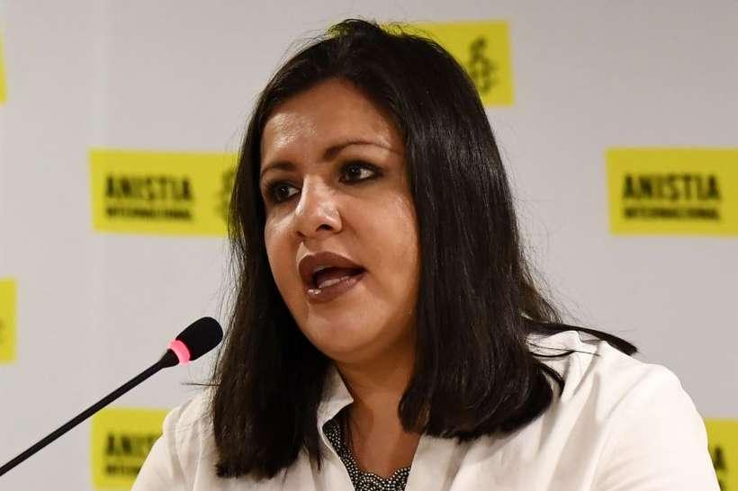 Erika Guevara Rosas- mulher branca, de cabelo preto, vestindo camiseta branca- sentada discursando na frente de um microfone