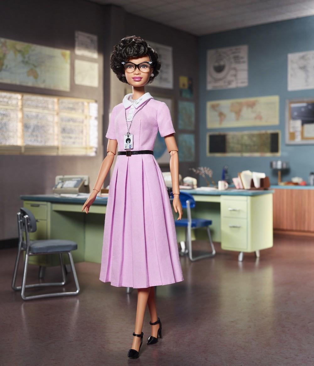 Barbie inspirada na cientista Katherine Johnson- boneca negra, usando óculos e vestido longo e rosa