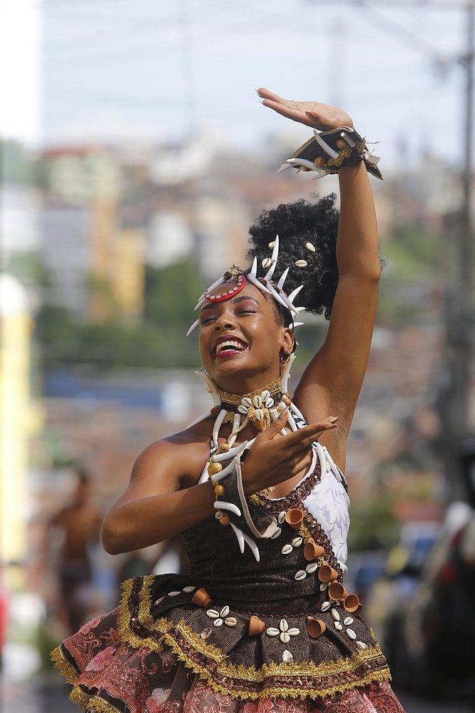 Gleicy Ellen Teixeira, mulher negra, de cabelo cacheado, dançando