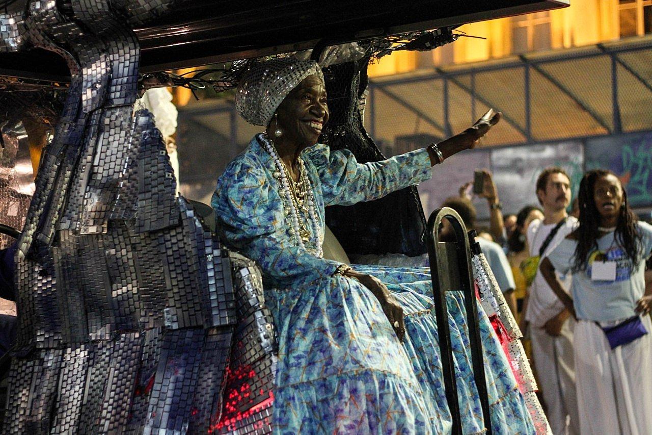 Lia de Itamaracá- mulher idosa negra, vestindo vestido azul, sentada em um carro alegórico