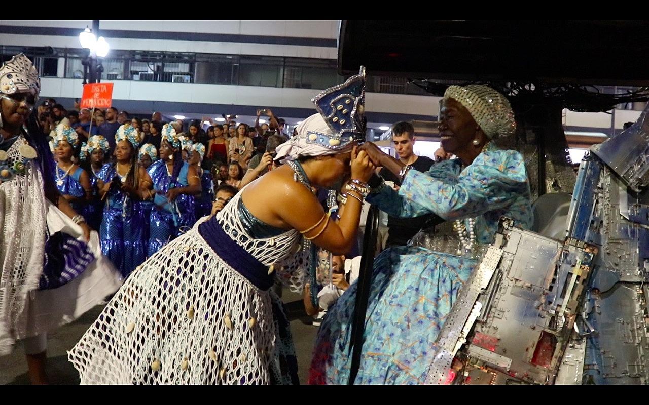 Lia de Itamaracá sendo cumprimentada por uma mulher