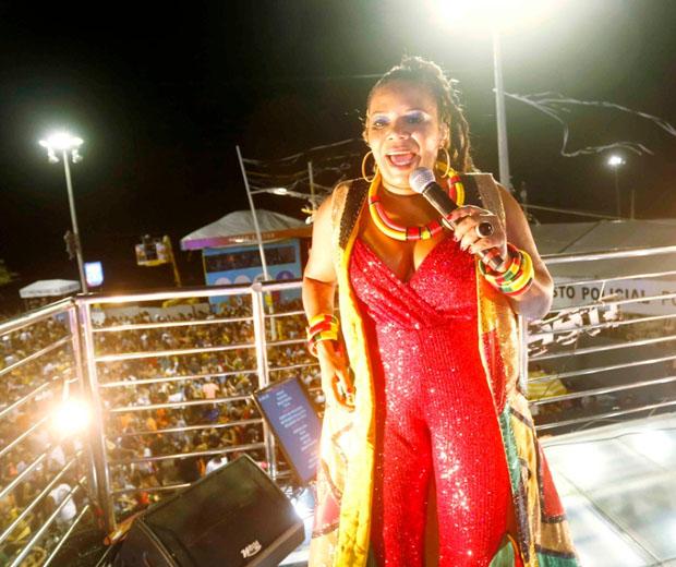 A cantora Margareth Menezes vestindo um luxuoso macacão vermelho em paetê e um max colete dourado com recortes assimétricos em preto e verde