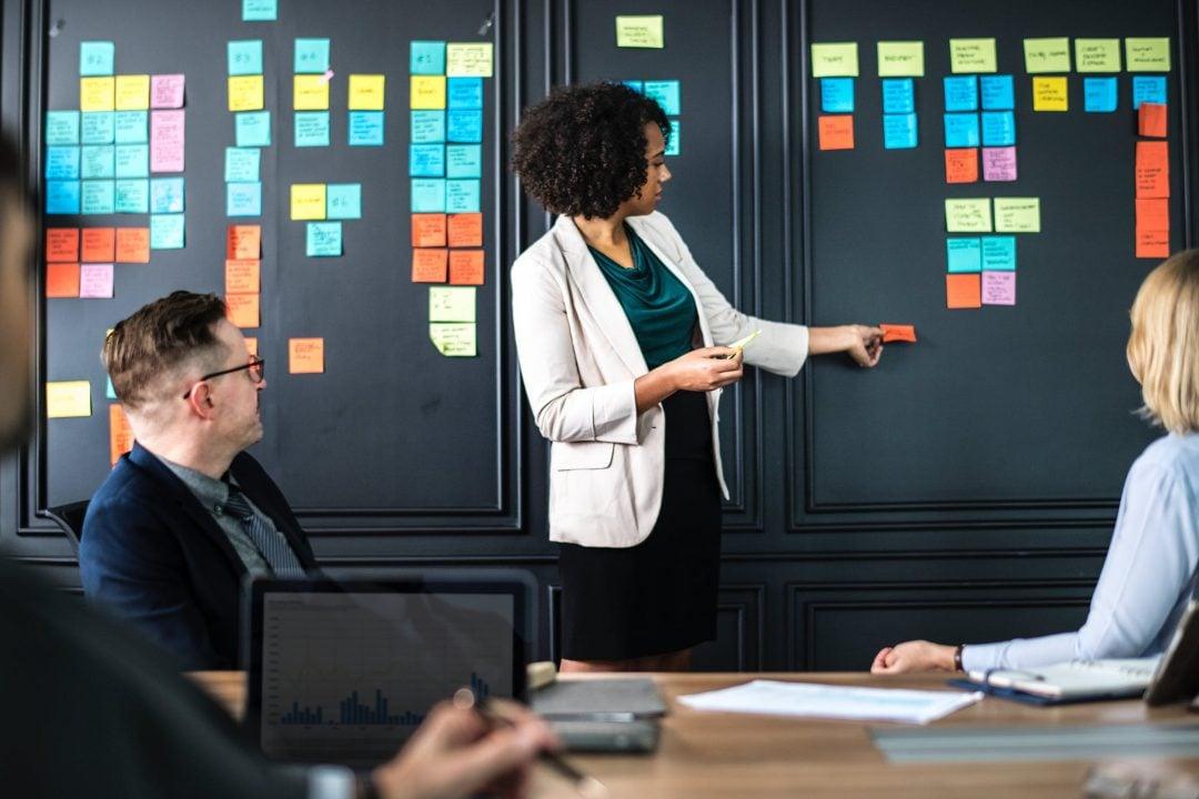 Imagem de uma mulher negra- vestindo roupa social- apresentando um projeto durante reunião