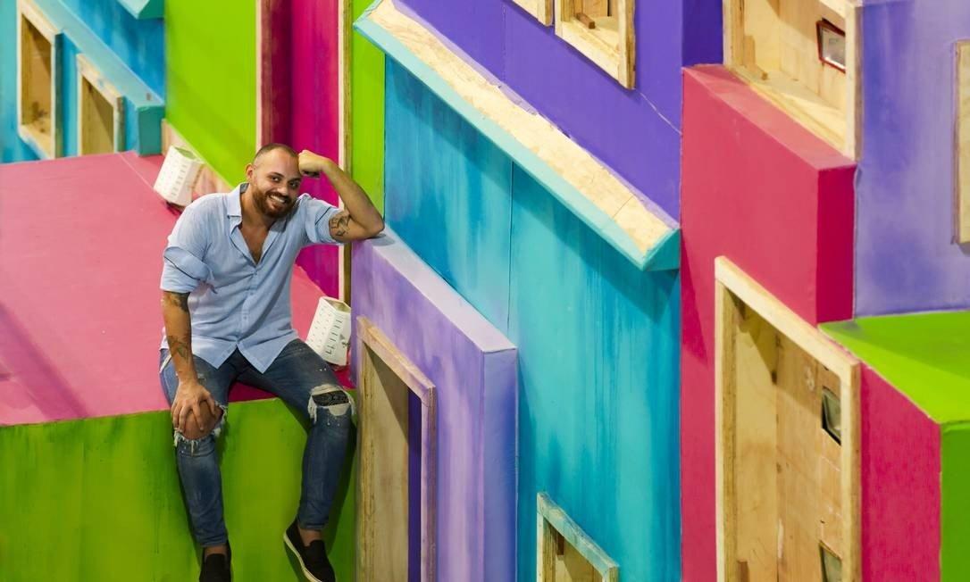 O carnavalesco Leandro Vieira - homem negro, careca, vestindo calça jeans e camiseta- sentado sorrindo