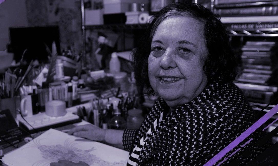 Foto de Rosa Magalhães- mulher idosa branca, vestindo camiseta com estampa preto e branca- sentada