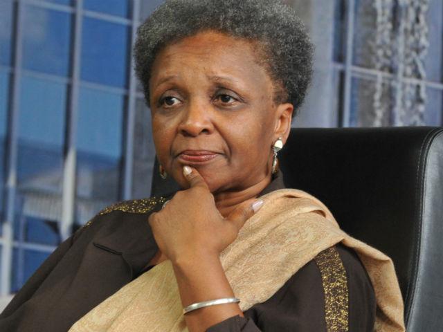 Foto de Luiza Bairros- mulher negra, usando camiseta marrom- sentada com a mão esquerda no queixo