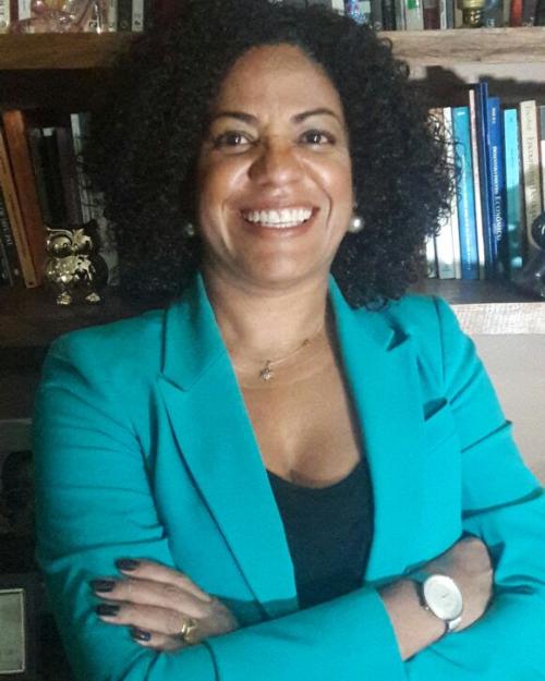 Maria do Carmo Rebouças dos Santos- mulher negra, de canelo cacheado, vestindo camiseta preta e casaco verde água- em pé sorrindo