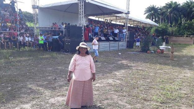 Luzia Maria - mulher idosa, vestindo camisa saia cor de rosa- em pé
