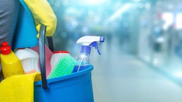 Imagem de uma mão com luva de borracha, segurando um balde cheio de produtos de limpeza